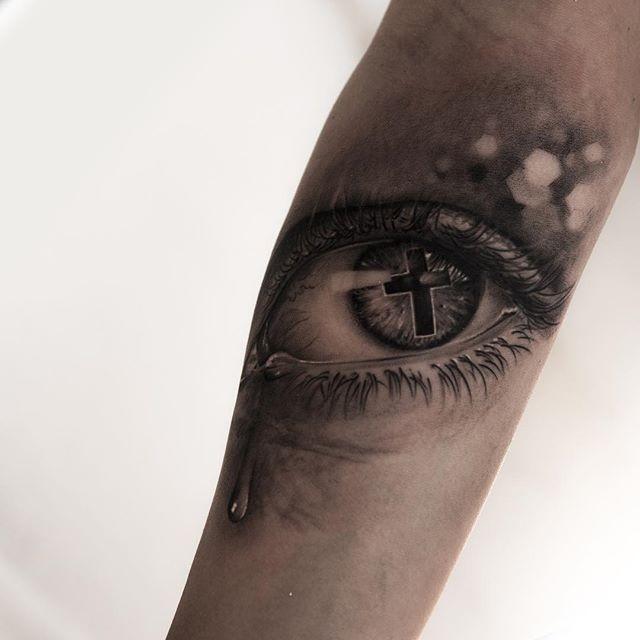kreuz in tr nenreichem auge tattoo am arm von niki norberg. Black Bedroom Furniture Sets. Home Design Ideas